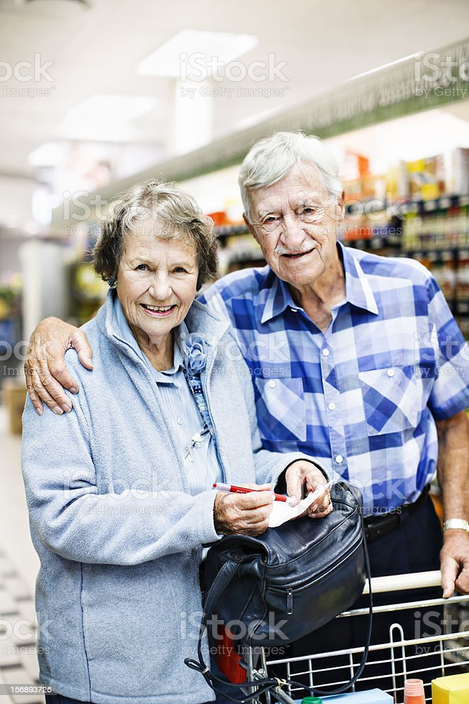 Cheerful senior couple check shoping list in supermarket stock photo