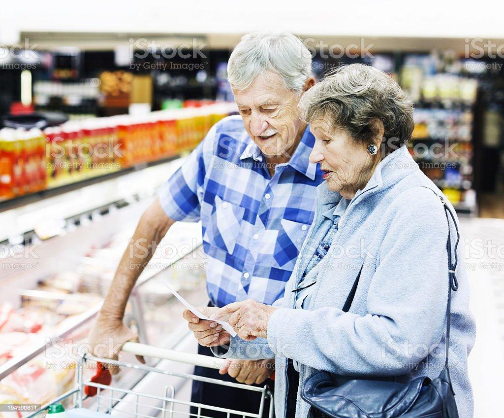 Cheerful senior couple check their shopping list in supermarket stock photo