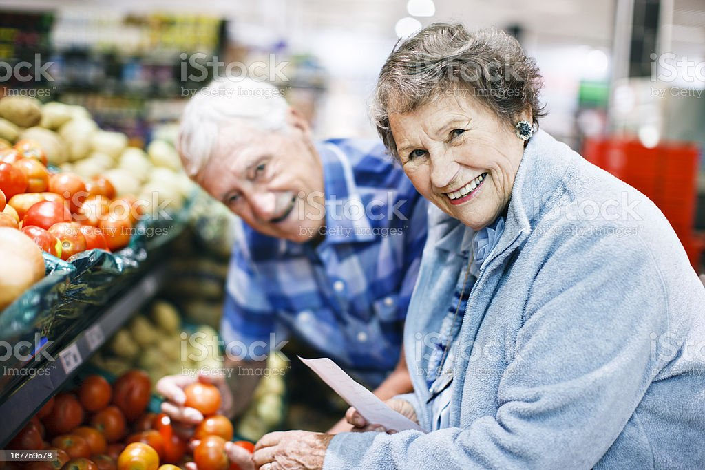 Cheerful senior couple choose vegetables in the supermarket stock photo