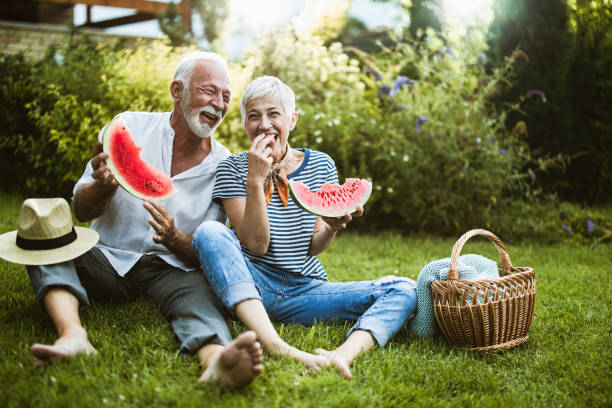Cheerful senior couple having fun while eating watermelon in the backyard. Cheerful mature couple having fun while eating watermelon during picnic day in their backyard. picnic stock pictures, royalty-free photos & images