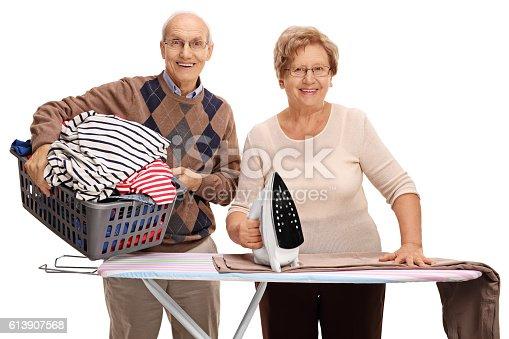 802472024 istock photo Cheerful senior couple ironing together 613907568