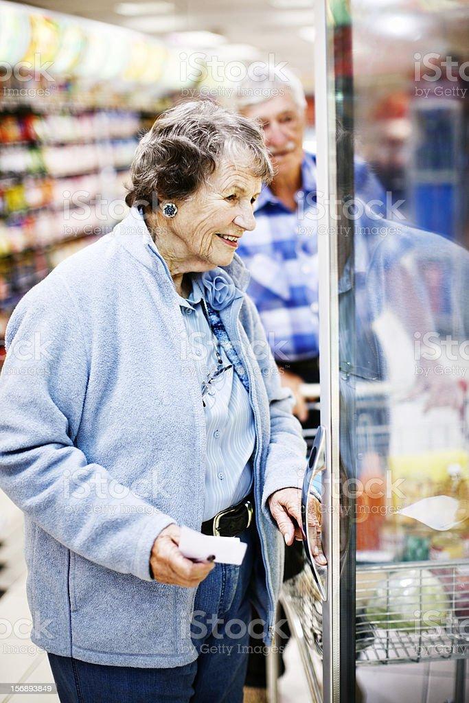 Cheerful senior couple look in supermarket fridge stock photo