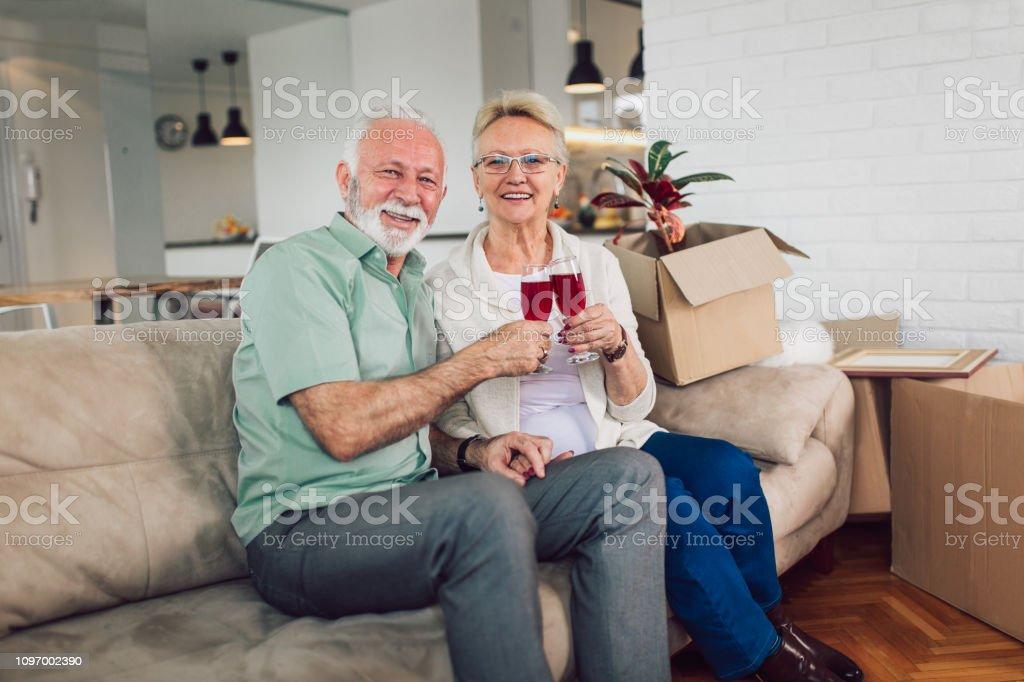 Pareja senior alegre en nueva casa sonriendo unos a otros y beber vino. - foto de stock