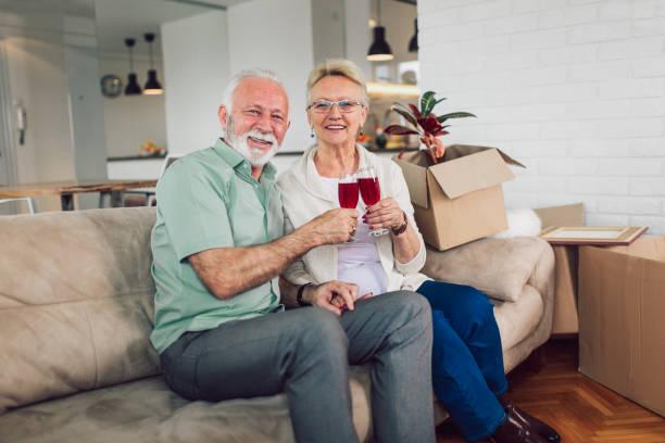fröhliche älteres paar einzug in die neue heimat lächelnd an einander und trinken wein. - seniorenwohnungen stock-fotos und bilder