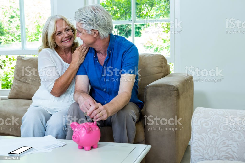Cheerful senior couple putting coin in piggi bank at home stock photo