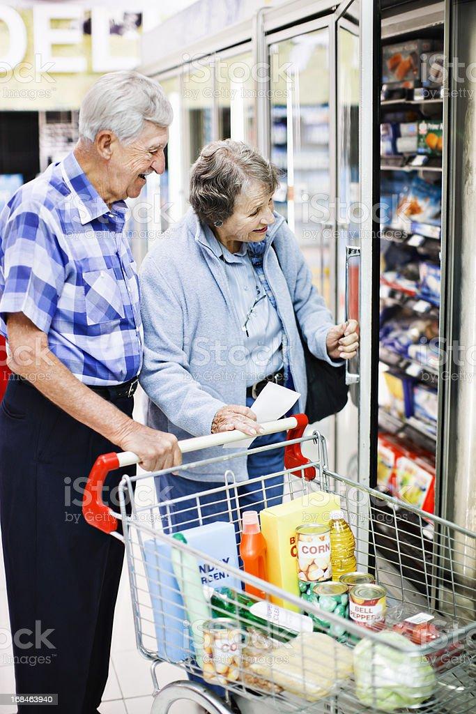 Cheerful senior couple shopping together check supermarket fridge stock photo