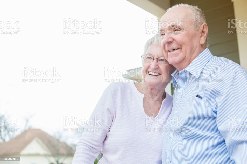 Cheerful senior couple stand together on front porch stock photo