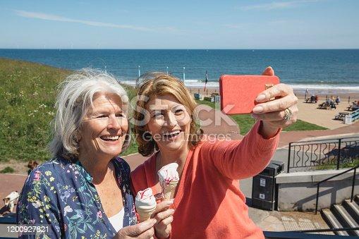 612518776 istock photo Cheerful senior female friends taking selfie at seaside 1200927821
