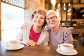 Cheerful positive attractive senior lady friends sitting at table with cups and embracing while looking at camera in coffee shop