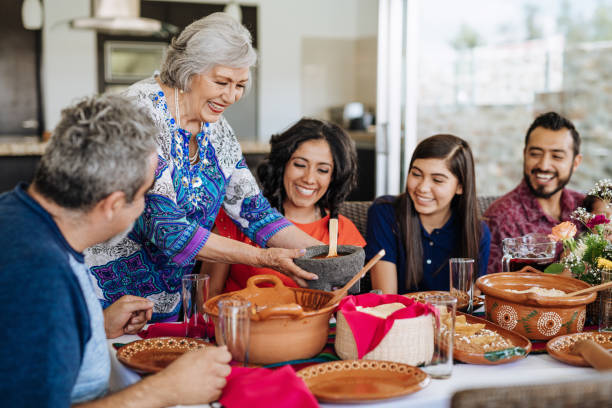 Cheerful senior Latin woman preparing lunch for her family stock photo
