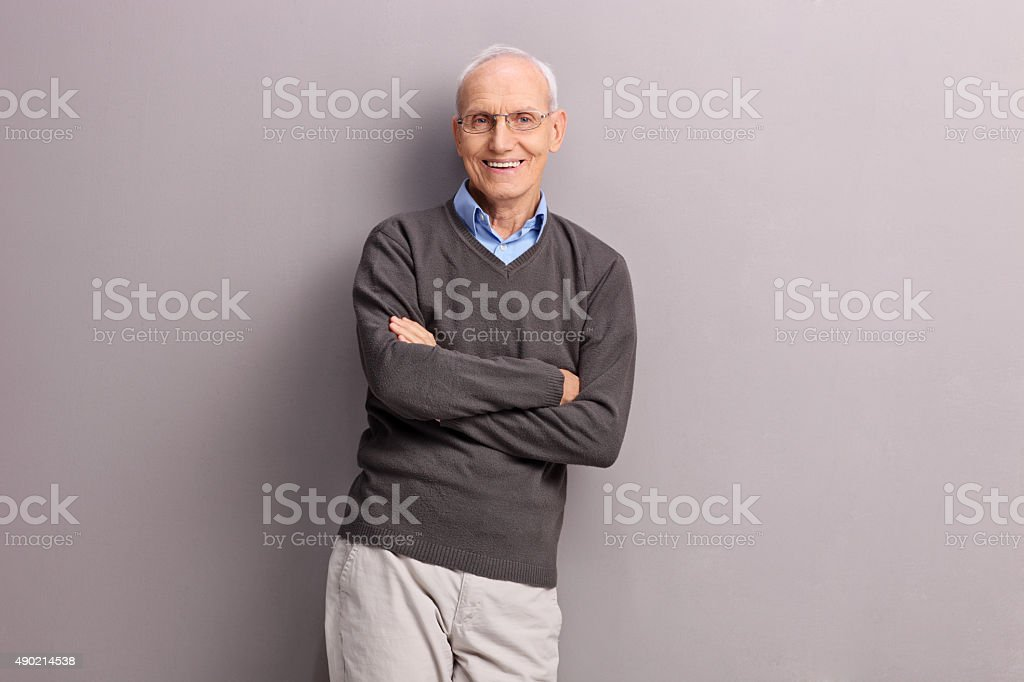 Cheerful senior leaning against a gray wall stock photo