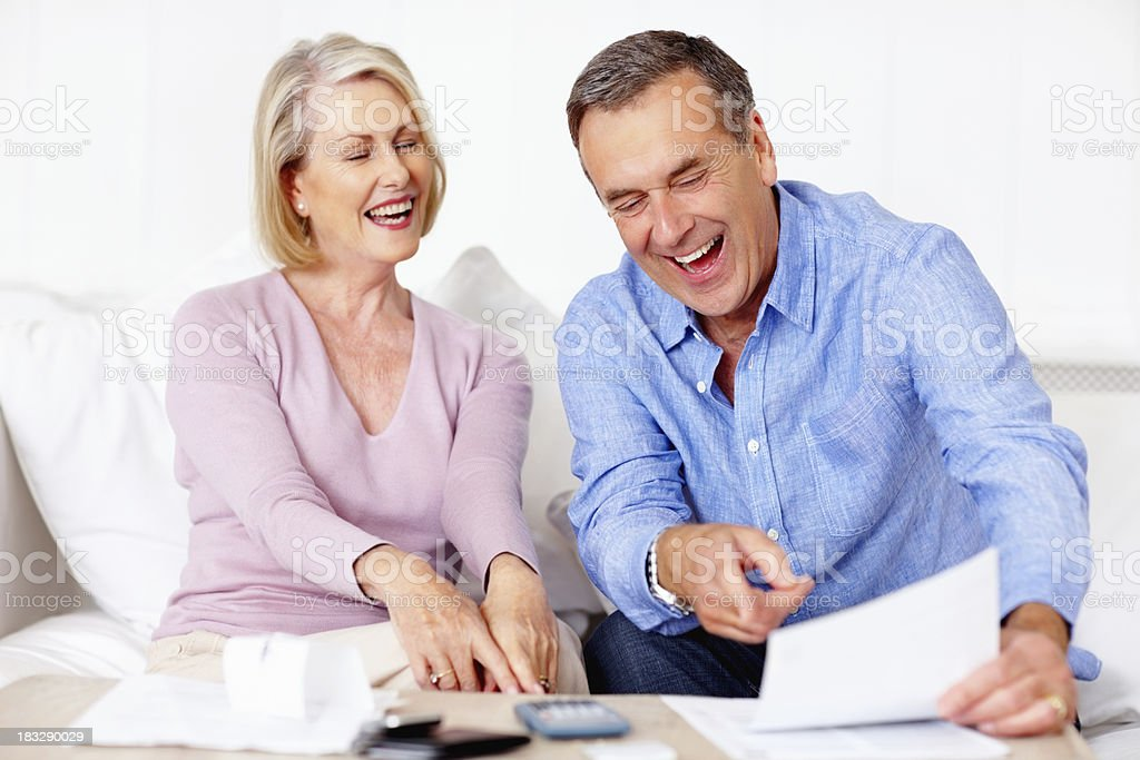 Cheerful senior man and woman calculating their home expenses royalty-free stock photo