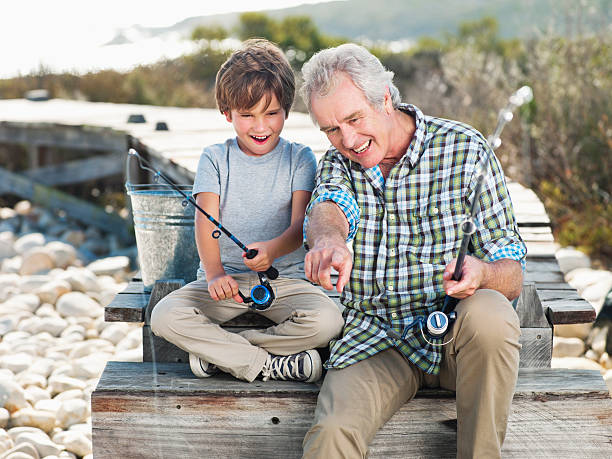 cheerful senior man fishing with boy on pier - baby boomers stock pictures, royalty-free photos & images