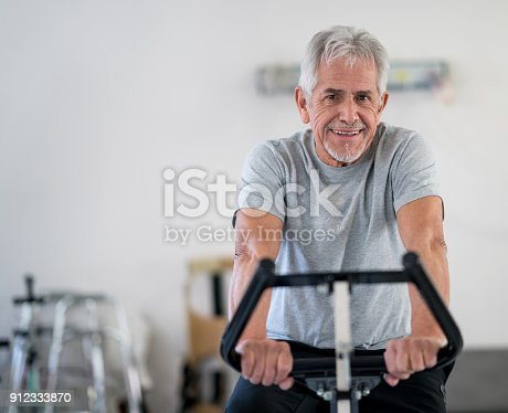 istock Cheerful senior man on a static bike at physiotherapy looking at camera smiling 912333870