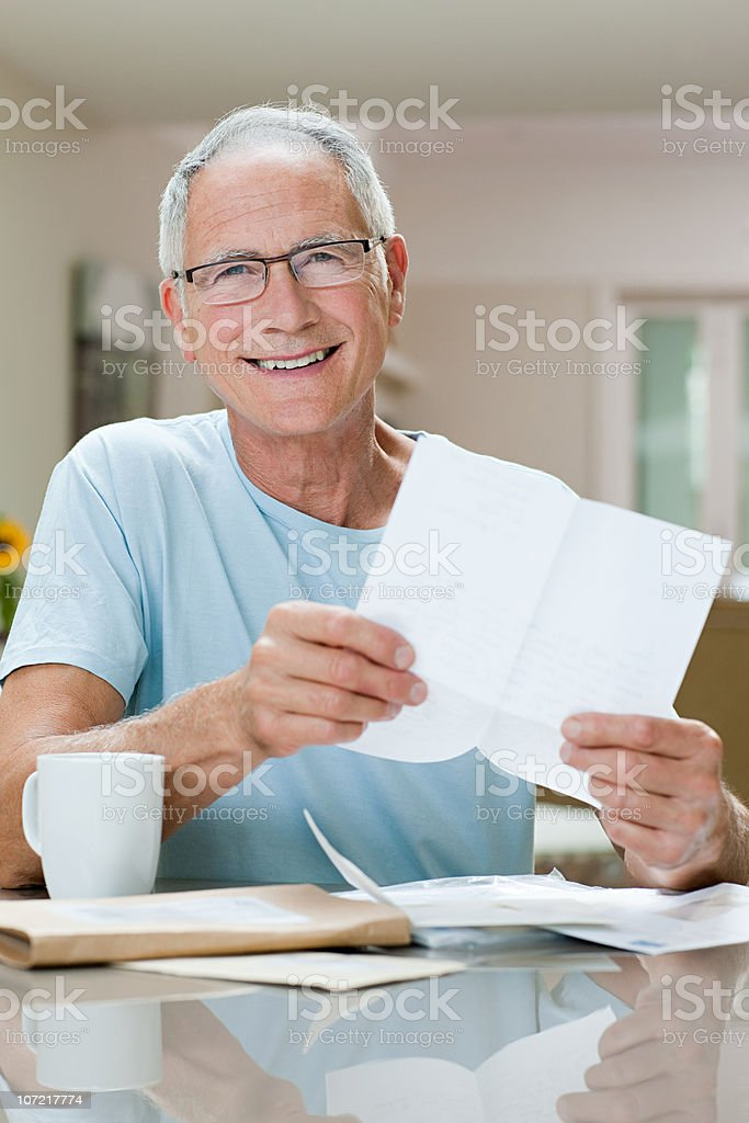Cheerful senior man reading letter royalty-free stock photo