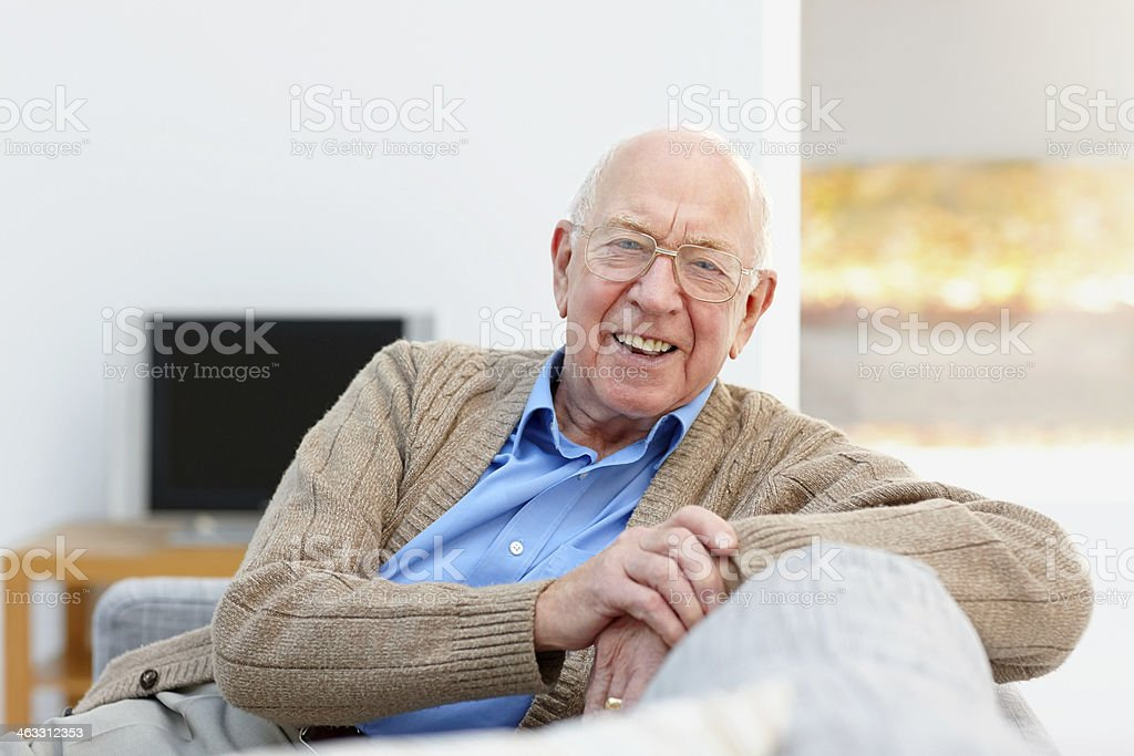Fröhlich alter Mann, sitzend auf couch – Foto