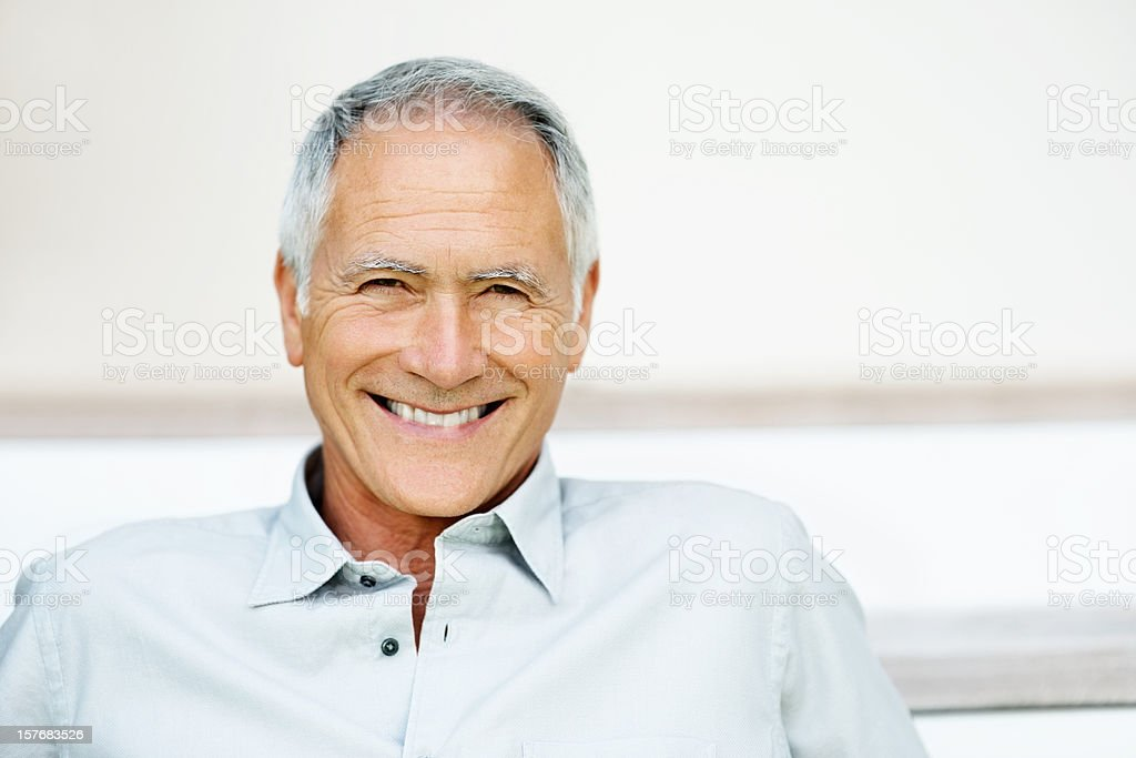 Cheerful senior man smiling against colored background royalty-free stock photo