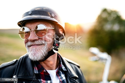 A front, view portrait of cheerful senior man traveller with motorbike in countryside, headshot.