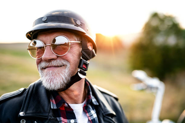 a cheerful senior man traveller with motorbike in countryside, headshot. - enjoying wealthy life imagens e fotografias de stock