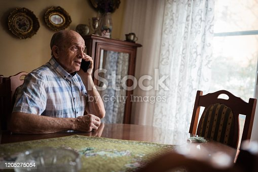 Old man talking on smart phone from home