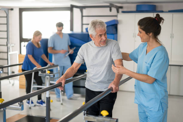 Cheerful senior man using parallel bars to walk and physiotherapist smiling at him happy stock photo