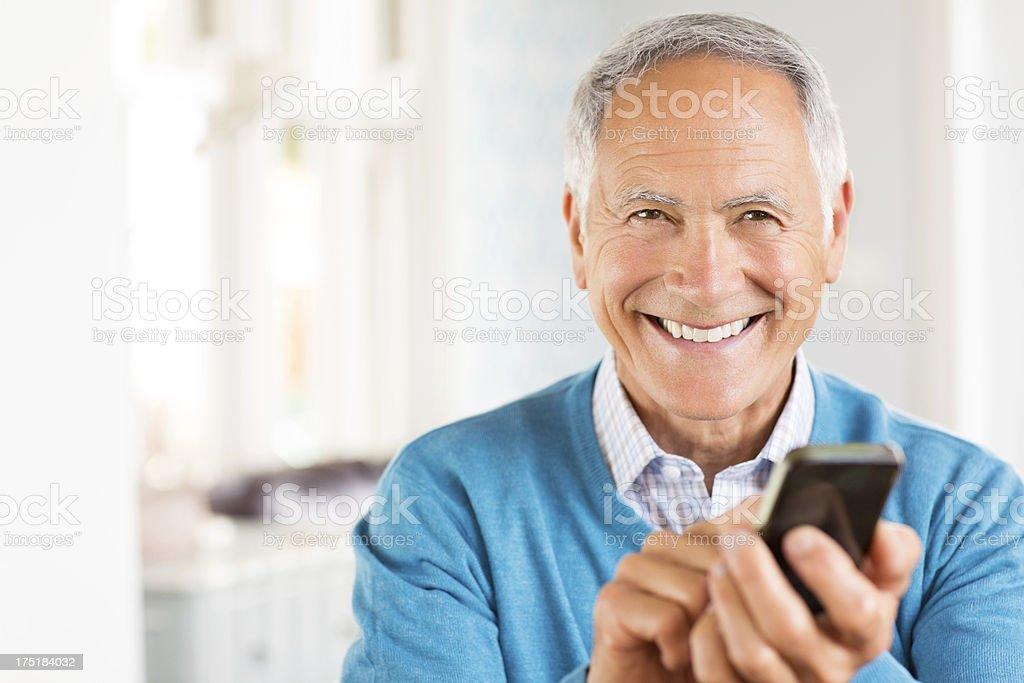 Cheerful Senior Man Using Smart Phone. stock photo