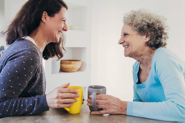 Fröhliche ältere Mutter und erwachsene Tochter teilen gute Nachrichten – Foto