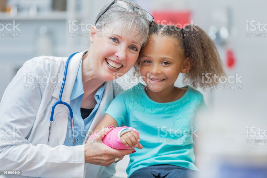 Cheerful senior pediatrician with patient stock photo