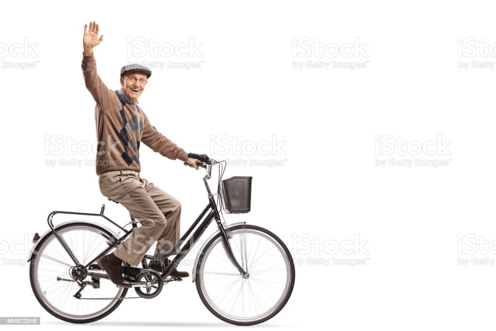 Cheerful senior riding a bicycle and waving at the camera royalty-free stock photo
