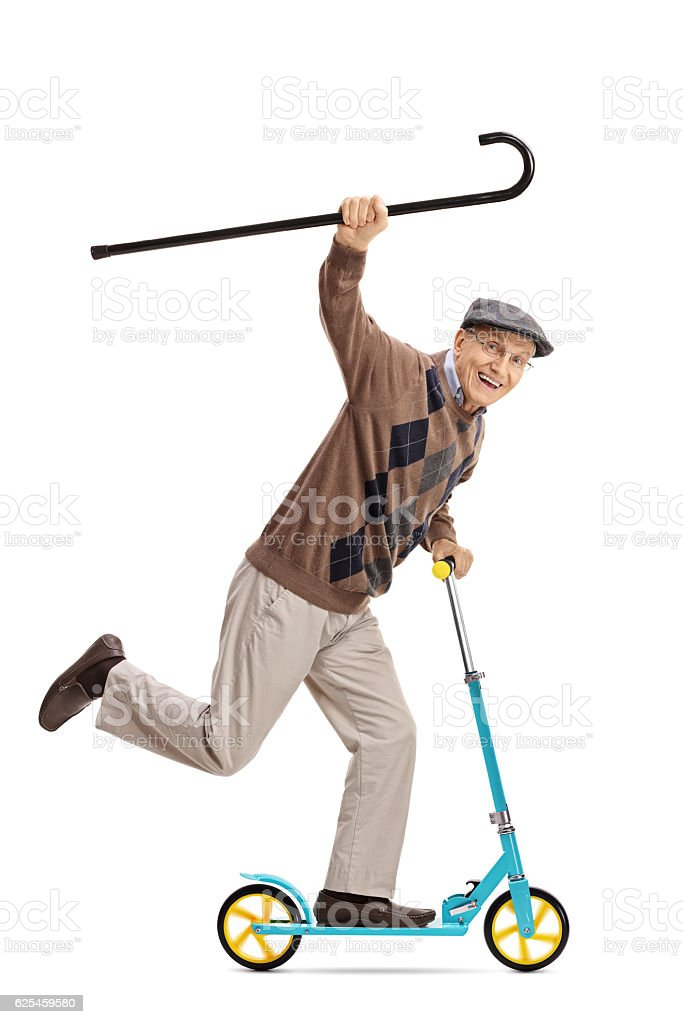 Cheerful senior riding a scooter and holding a walking cane stock photo