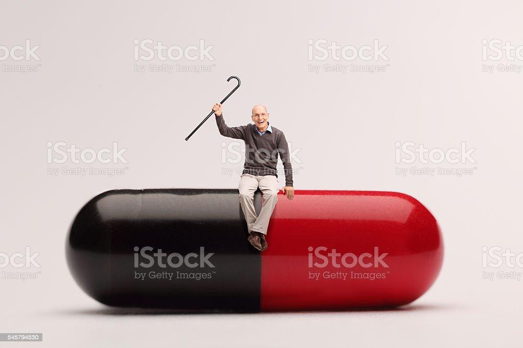 Cheerful senior sitting on a giant pill stock photo