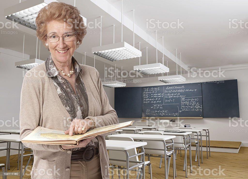 Cheerful senior teacher pointing to a book royalty-free stock photo