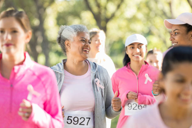 cheerful senior woman and her daughter during charity walk - fondazione di beneficienza foto e immagini stock