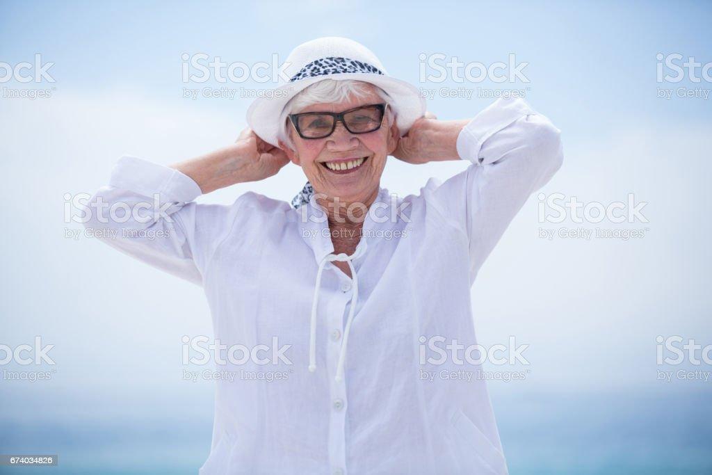 Cheerful senior woman at beach against sky royalty-free stock photo
