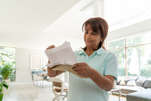 Cheerful senior woman at home checking her mail smiling