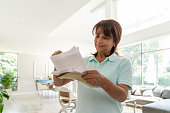 Cheerful senior woman at home checking her mail smiling - Low angle view