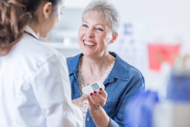 Cheerful senior woman discusses something with her doctor Smiling Caucasian female patient discusses diabetes with her doctor during medical appointment. endocrine system stock pictures, royalty-free photos & images