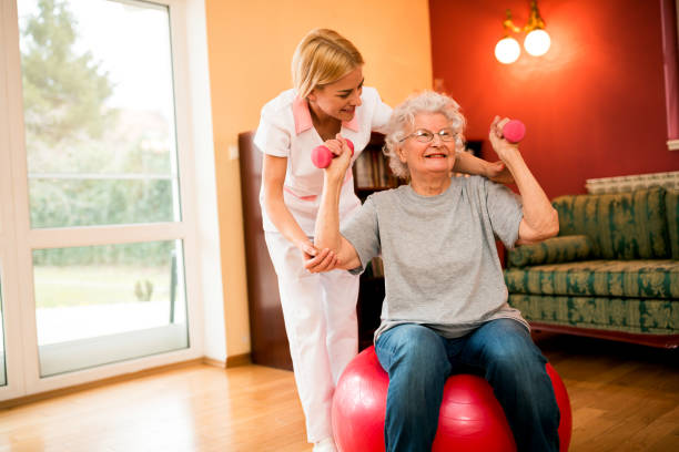 Cheerful senior woman exercising her arms with dumbbells stock photo
