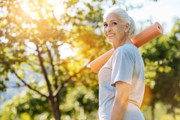 Cheerful senior woman going to enjoy yoga in the park stock photo