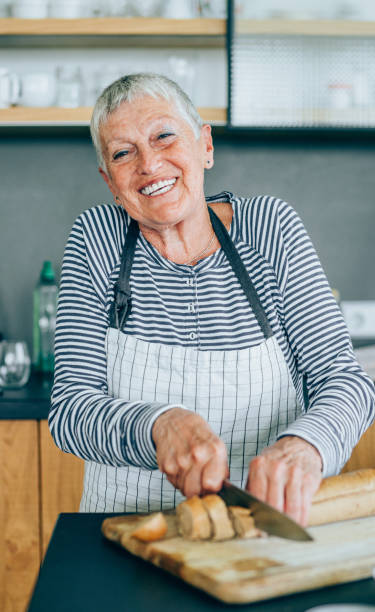 cheerful senior woman in the kitchen - violetastoimenova stock photos and pictures