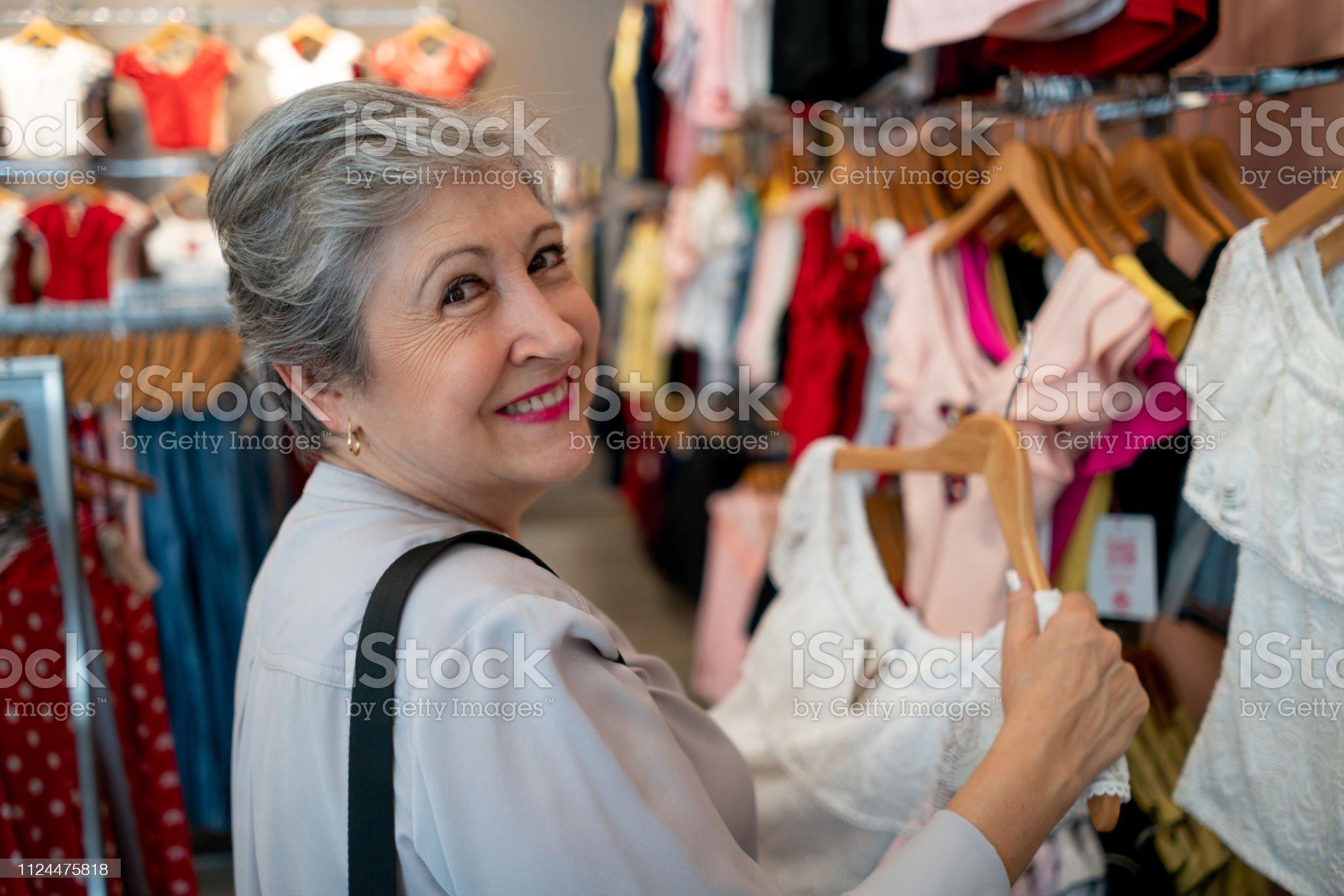 Imagen De Mujer Senior Alegre Mirando A Cámara Sonriendo Mientras Que Las Compras En Una Tienda De Ropa Fotografía De Stock