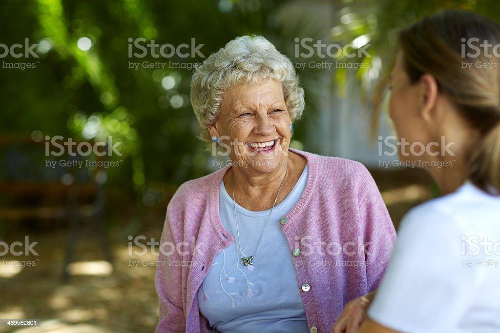 Cheerful senior woman looking at caretaker stock photo