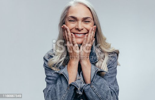 Cheerful senior woman with hands on her face against grey background. Happy mature woman in casual denim shirt.