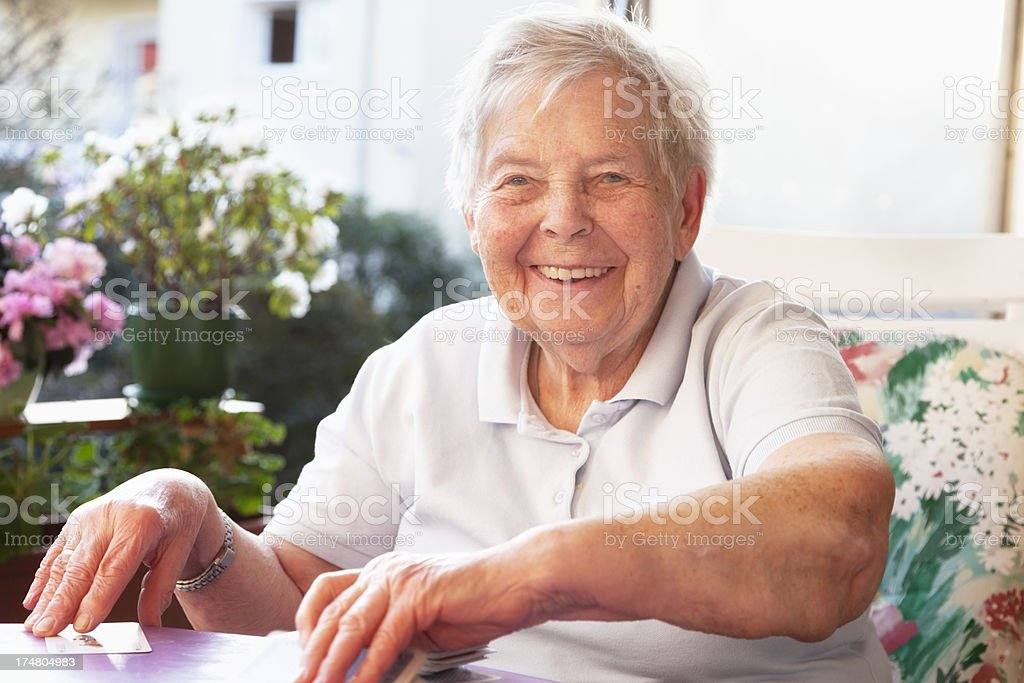 cheerful senior woman playing cards royalty-free stock photo