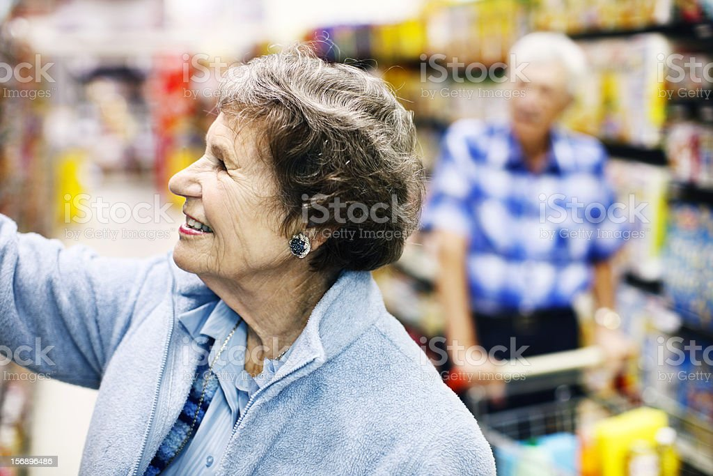 Cheerful senior woman shopping in supermarket with husband stock photo