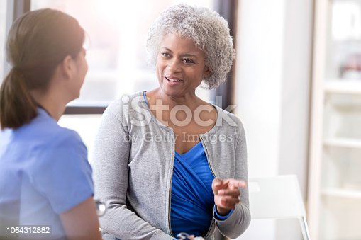 A cheerful senior woman sits beside his unrecognizable female doctor and gestures and points as she shares her symptoms.