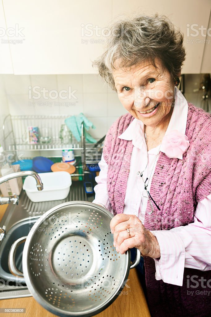 Cheerful senior woman washing colander at kitchen sink stock photo