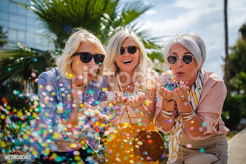 Fashionable mature friends having fun and celebrating by blowing colorful confetti in city street