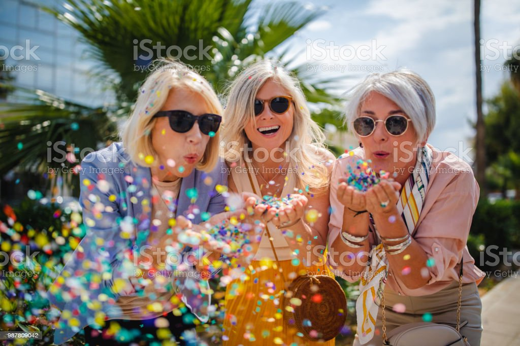 Cheerful senior women celebrating by blowing confetti in the city stock photo