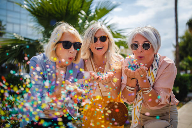 Cheerful senior women celebrating by blowing confetti in the city Fashionable mature friends having fun and celebrating by blowing colorful confetti in city street young at heart stock pictures, royalty-free photos & images